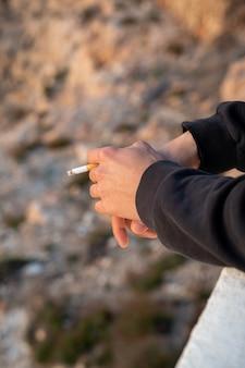 Uomo caucasico con una sigaretta in mano su una scogliera, palma de mallorca, spain