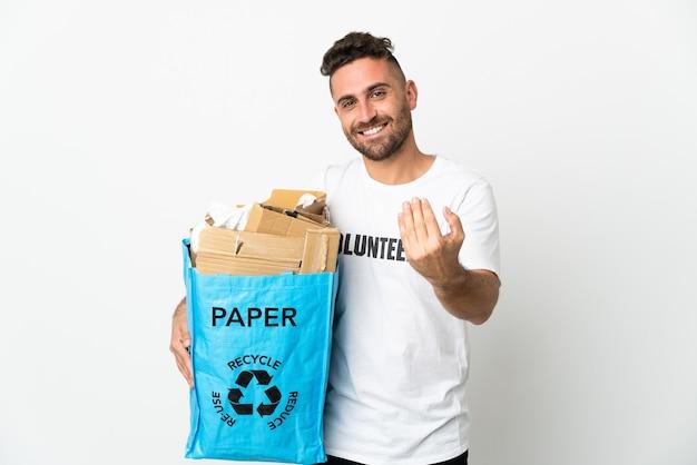 Uomo caucasico che tiene un sacchetto di riciclaggio pieno di carta da riciclare isolato su sfondo bianco che invita a venire con la mano. felice che tu sia venuto