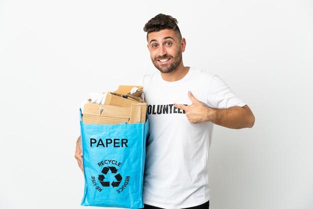 Uomo caucasico che tiene un sacchetto di riciclaggio pieno di carta da riciclare isolato sulla parete bianca con l'espressione facciale di sorpresa