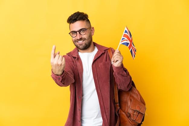 Uomo caucasico che tiene una bandiera del regno unito isolata su sfondo giallo facendo un gesto imminente