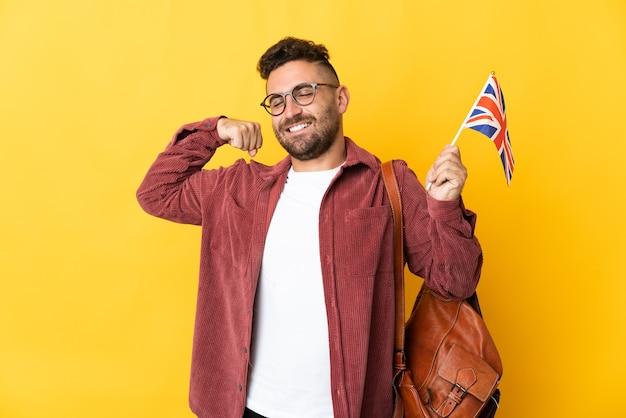Uomo caucasico che tiene una bandiera del regno unito isolata su sfondo giallo facendo un gesto forte