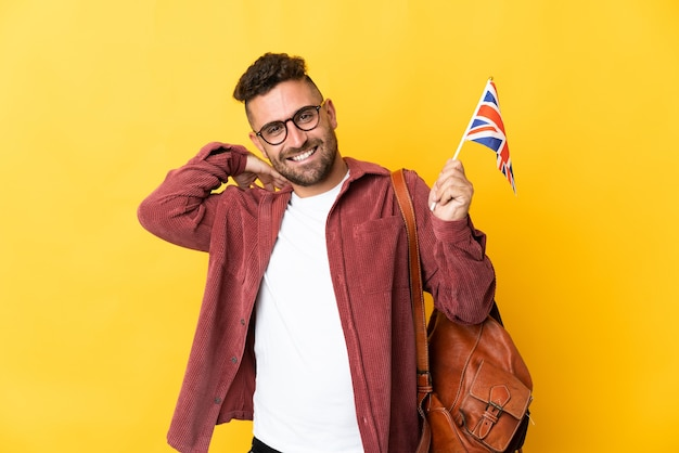 Uomo caucasico che tiene una bandiera del regno unito isolata su fondo giallo che ride