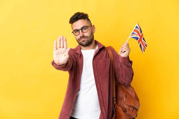 Uomo caucasico che tiene una bandiera del regno unito isolata su sfondo giallo facendo un gesto di arresto stop
