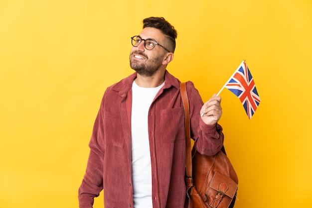 Uomo caucasico che tiene una bandiera del regno unito isolata su sfondo giallo pensando a un'idea mentre guarda in alto