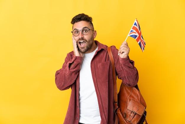 Uomo caucasico che tiene una bandiera del regno unito isolata su sfondo giallo con espressione facciale sorpresa e scioccata