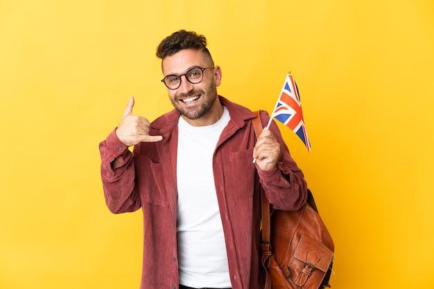 Uomo caucasico che tiene una bandiera del regno unito isolata sulla parete gialla che fa gesto del telefono. richiamami segno
