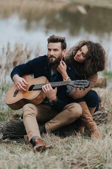 L'uomo caucasico sta suonando la chitarra con la donna in riva al lago. la giovane coppia sta abbracciando il giorno di autunno all'aperto. un uomo barbuto e una donna riccia innamorata.