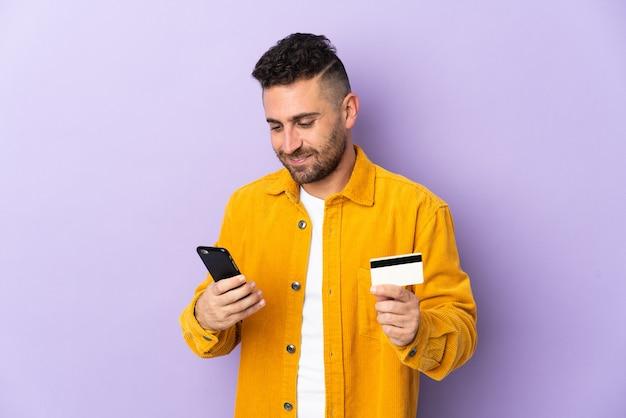 Uomo caucasico isolato su sfondo viola che acquista con il cellulare con una carta di credito