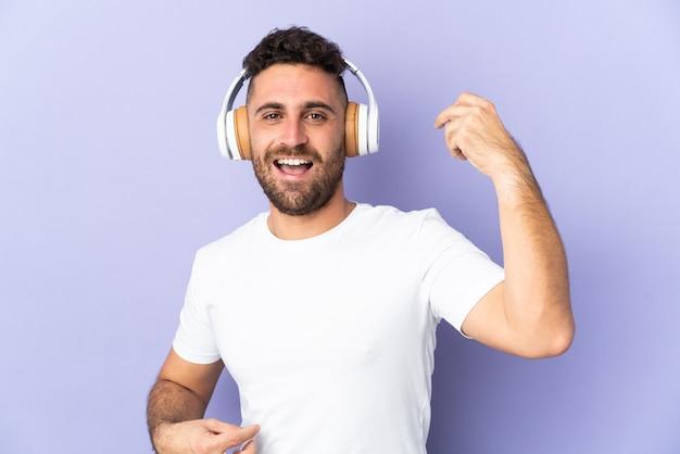Uomo caucasico isolato su sfondo viola ascoltando musica e facendo il gesto della chitarra