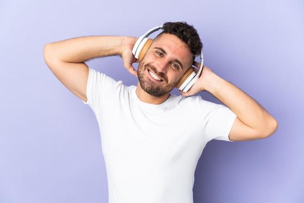 Uomo caucasico isolato su sfondo viola ascoltando musica
