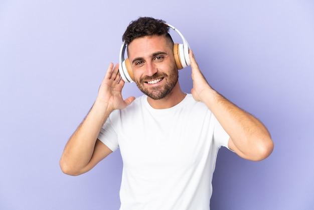 Uomo caucasico isolato sulla musica d'ascolto della parete viola