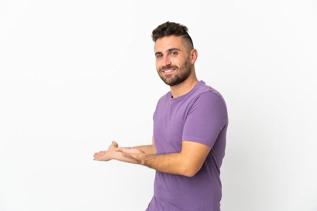 Uomo caucasico isolato su sfondo bianco che estende le mani a lato per invitare a venire