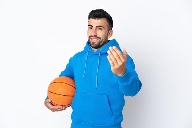 Uomo caucasico sopra la parete bianca isolata che gioca a basket e che fa il gesto in arrivo