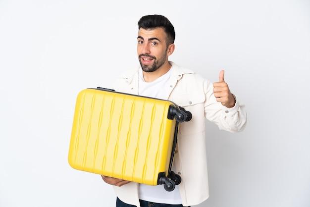 Uomo caucasico sopra la parete bianca isolata in vacanza con la valigia di viaggio e con il pollice in su