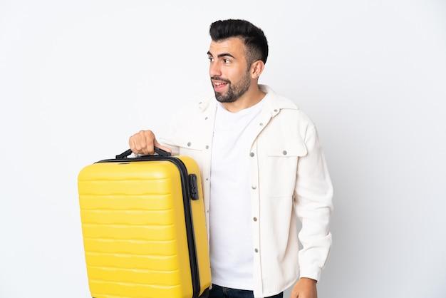 Uomo caucasico sopra la parete bianca isolata in vacanza con la valigia di viaggio