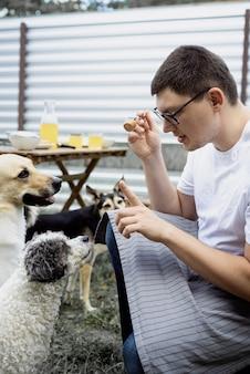 Uomo caucasico che bacia un cane, cammina all'aperto nel cortile sul retro