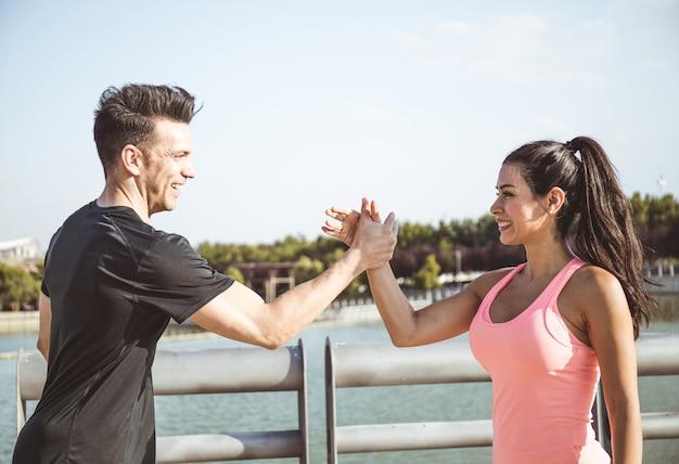 Un uomo caucasico e una donna latina si salutano prima di iniziare a fare sport sulla sponda di un lago in un parco della città di madrid.