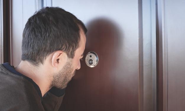 Uomo caucasico guardando attraverso lo spioncino.