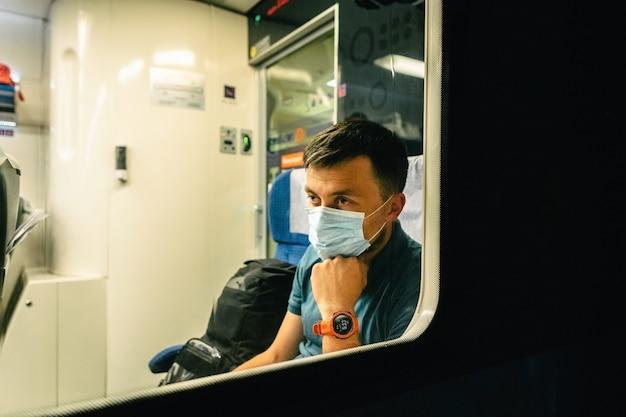 L'uomo caucasico guarda fuori dal finestrino di un treno notturno con uno sguardo triste in una mascherina medica