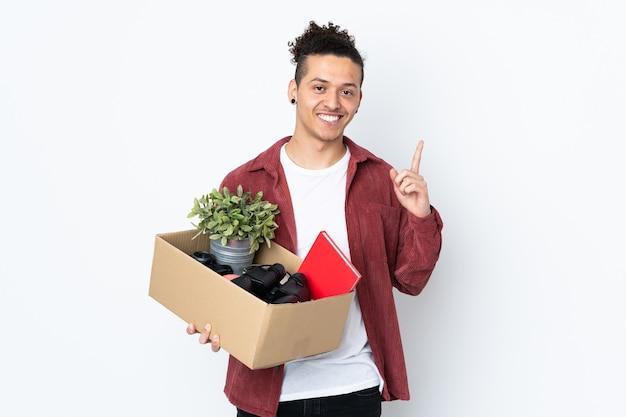 L'uomo caucasico fa una mossa mentre prende una scatola piena di cose sul muro bianco isolato che intende realizzare la soluzione mentre alza un dito