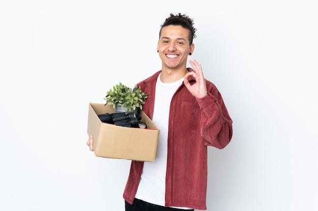 Uomo caucasico che fa una mossa mentre prende in mano una scatola piena di cose sul muro bianco isolato che mostra il segno giusto con le dita
