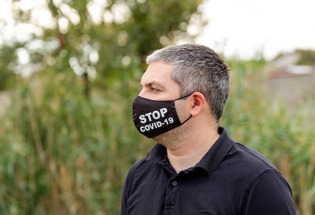 Uomo caucasico in una maschera facciale medica contro l'inquinamento atmosferico