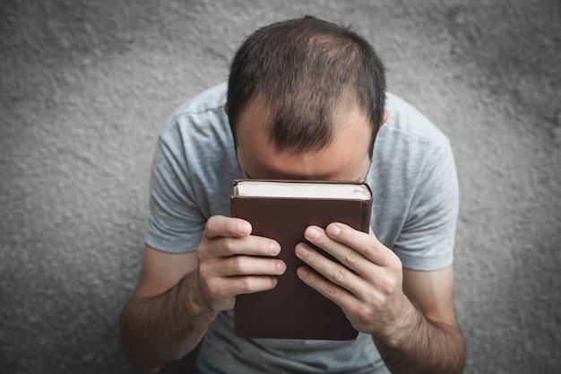 Uomo caucasico che prega sopra la bibbia. religione