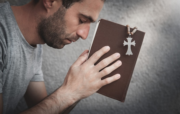 Uomo caucasico che prega sopra la bibbia.