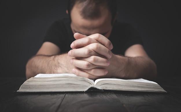 Uomo caucasico che prega nella stanza buia