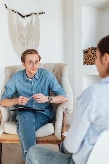 Psicologo uomo caucasico in occhiali seduto su una sedia sul posto di lavoro, ascolta il paziente e prende appunti.
