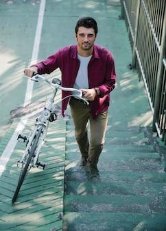 Uomo caucasico che spinge la sua bicicletta su per la collina
