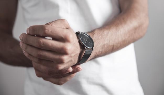L'uomo caucasico mette su un orologio da polso