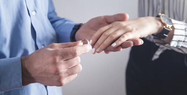 Uomo caucasico che mette sull'anello di fidanzamento del dito della ragazza. Foto Premium