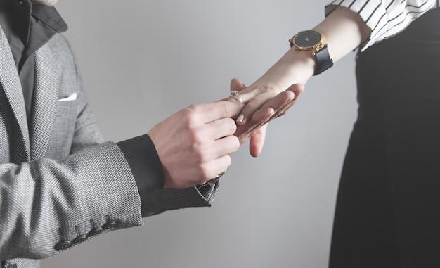 Uomo caucasico che mette sull'anello di fidanzamento del dito della ragazza.