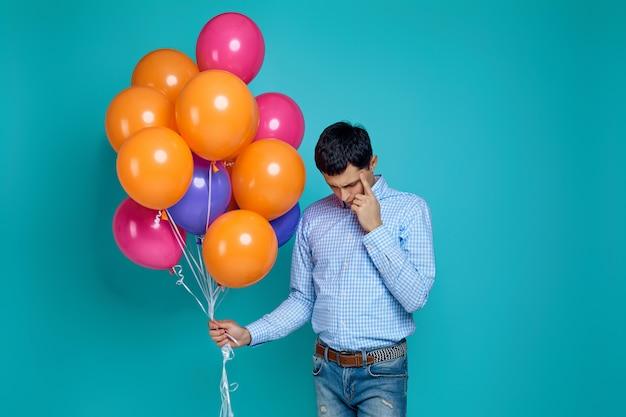 Uomo caucasico in camicia con palloncini colorati luminosi pensando a somethinh isolato su blu
