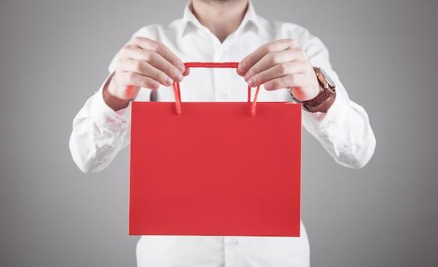 Uomo caucasico che mostra il sacchetto della spesa rosso.