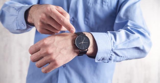 Uomo caucasico che mostra orologio da polso in ufficio.