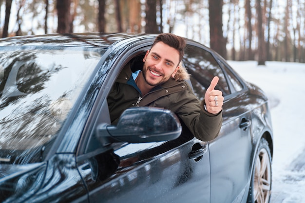 L'uomo caucasico si siede al volante della sua auto soleggiata