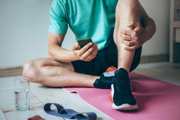 L'uomo caucasico seduto sul pavimento mentre ci si rilassa dopo aver fatto fitness a casa sta usando un telefono e un bicchiere d'acqua