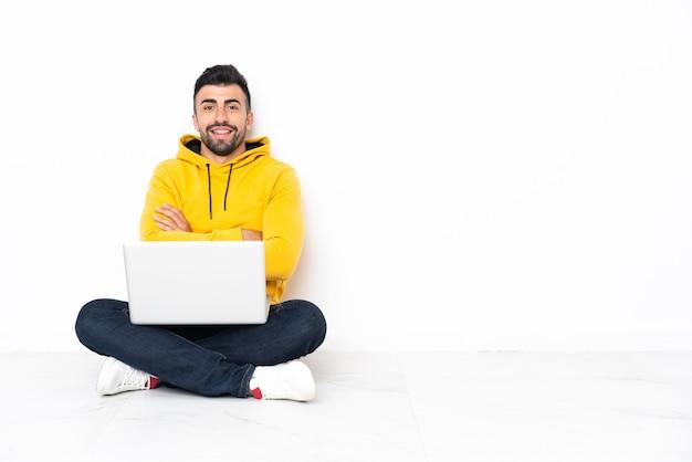 Uomo caucasico seduto sul pavimento con il suo laptop mantenendo le braccia incrociate in posizione frontale