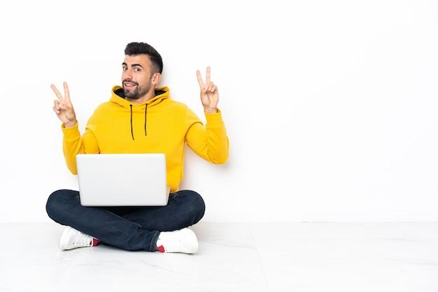 Uomo caucasico che si siede sul pavimento con il suo computer portatile che mostra il segno di vittoria con entrambe le mani