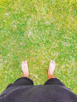 Uomo caucasico in piedi sull'erba guardando i suoi piedi. palma di maiorca, spagna