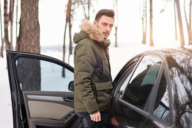 L'uomo caucasico si trova nella foresta invernale vicino alla sua auto