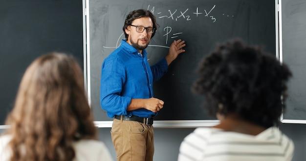 Insegnante dell'uomo caucasico alla scuola che scrive formule e leggi matematiche sulla lavagna. concetto di scuola. docente maschio in bicchieri che spiega le leggi della matematica agli alunni. concetto educativo.