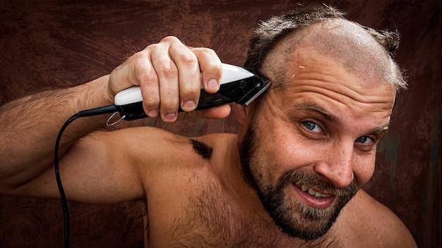 Uomo caucasico che cerca di radersi la testa con un rasoio elettrico.