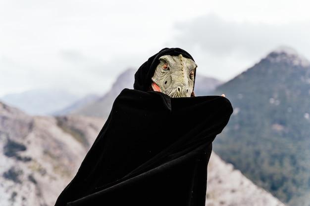 Uomo caucasico che indossa una maschera di dinosauro arrabbiato e un mantello nella catena montuosa della sierra de tramuntana. palma di maiorca, spagna