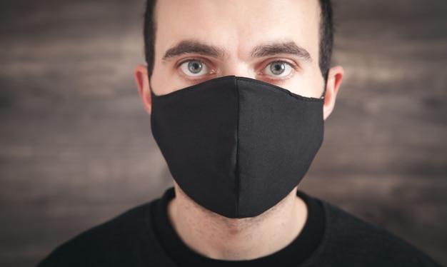 Uomo caucasico che indossa la maschera facciale nera.
