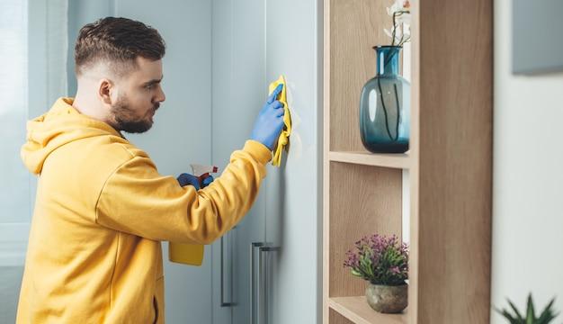 L'uomo caucasico che indossa guanti blu sta pulendo la casa usando un panno e uno spray disinfettante