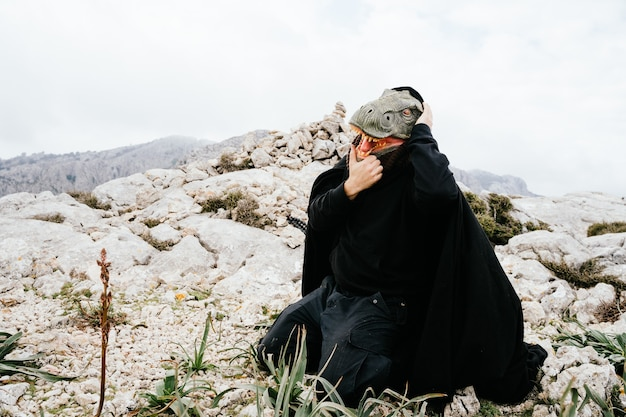 Uomo caucasico che indossa una maschera di dinosauro e un mantello, triste, urlando e tenendo le mani alla testa nella catena montuosa della sierra de tramuntana, palma de mallorca, spagna