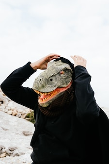 Uomo caucasico che indossa una maschera di dinosauro e un capo sorpreso e tenendo le mani alla testa nella sierra de tramuntana, palma de mallorca, spagna